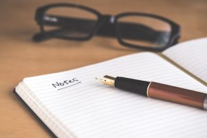 a black glasses, a pen, and a notebook with the word 'notes' written on it, are all on top of a wooden desk