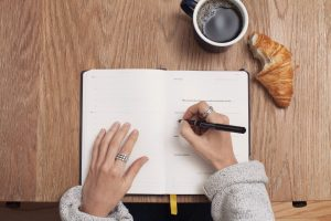 a female employee's hands are shown on top of the desk with a croissant and a coffee while she's writing notes