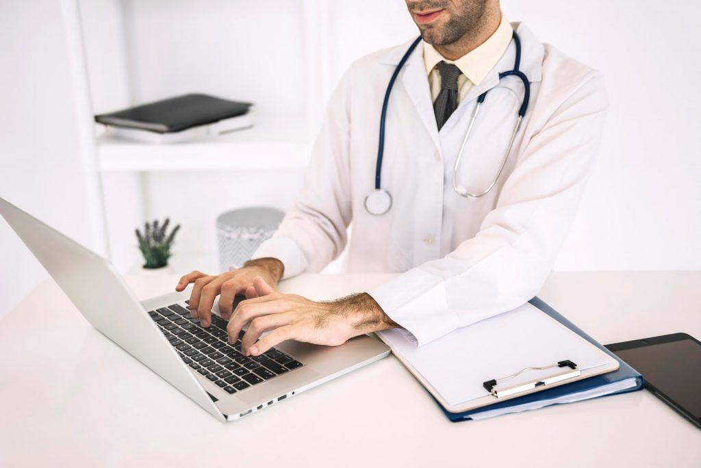 male medical professional typing medical transcriptions on a laptop beside documents on a clipboard