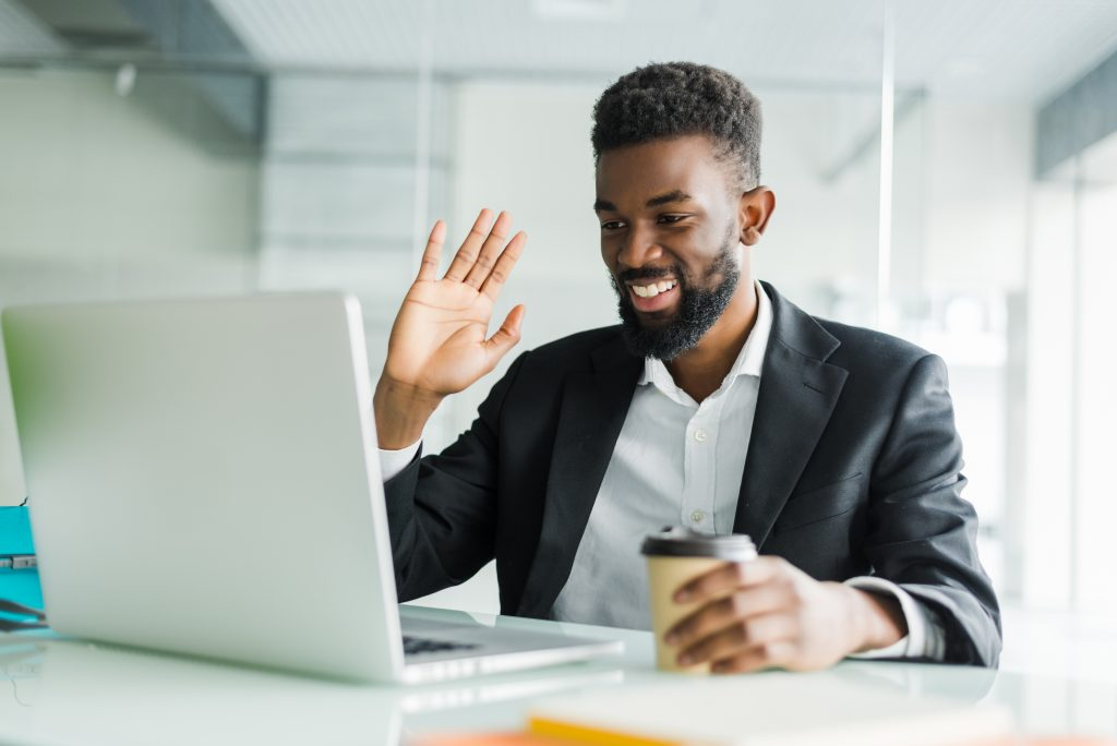 Young African American manager with stubble sitting in front of open laptop wearing earphones while having video conference call with business partners