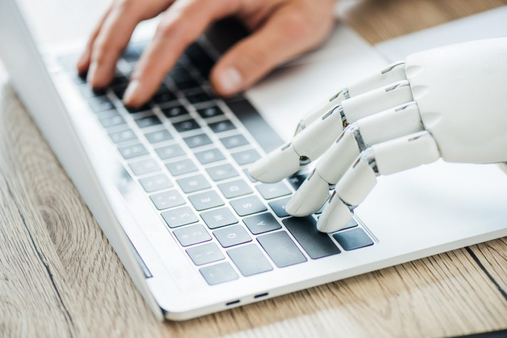 Human and robot hand typing on a laptop