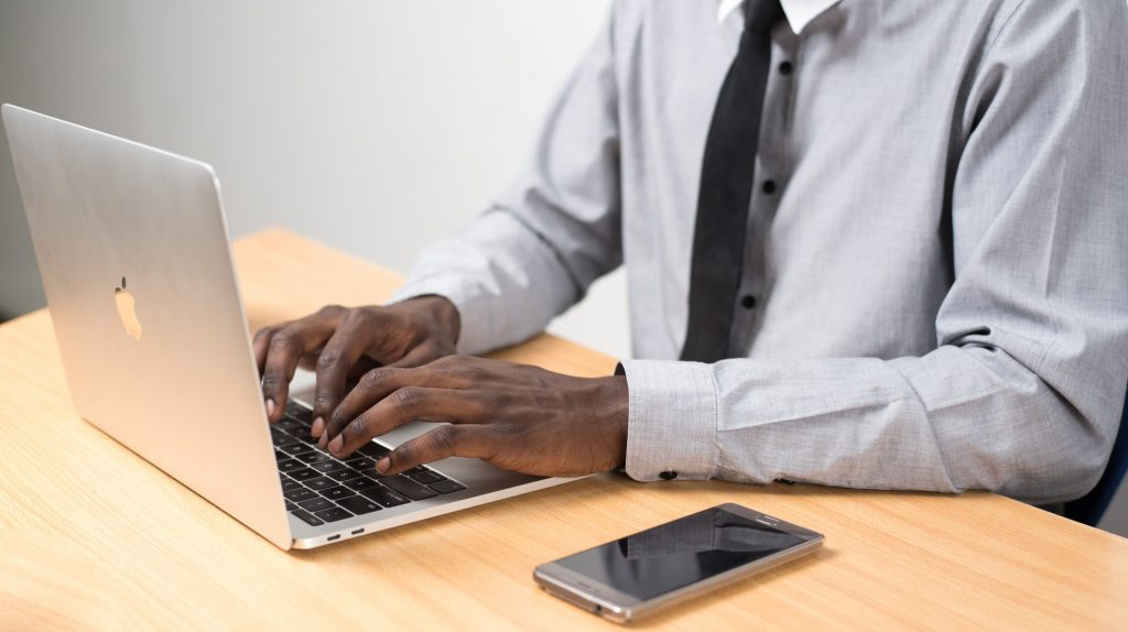 Expert from human transcriptionist services typing on laptop